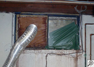 A basement window system that's rotted and  has been damaged over time in Beverly.