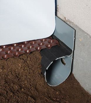 Closeup of a crawl space drainage system installed in Dracut