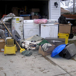 Soaked, wet personal items sitting in a driveway, including a washer and dryer in Framingham.